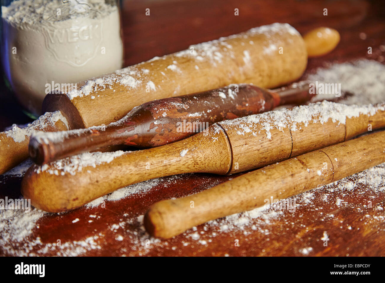 vintage rolling pins covered in flour over a wood table with a glass jar of flour - Stock Image
