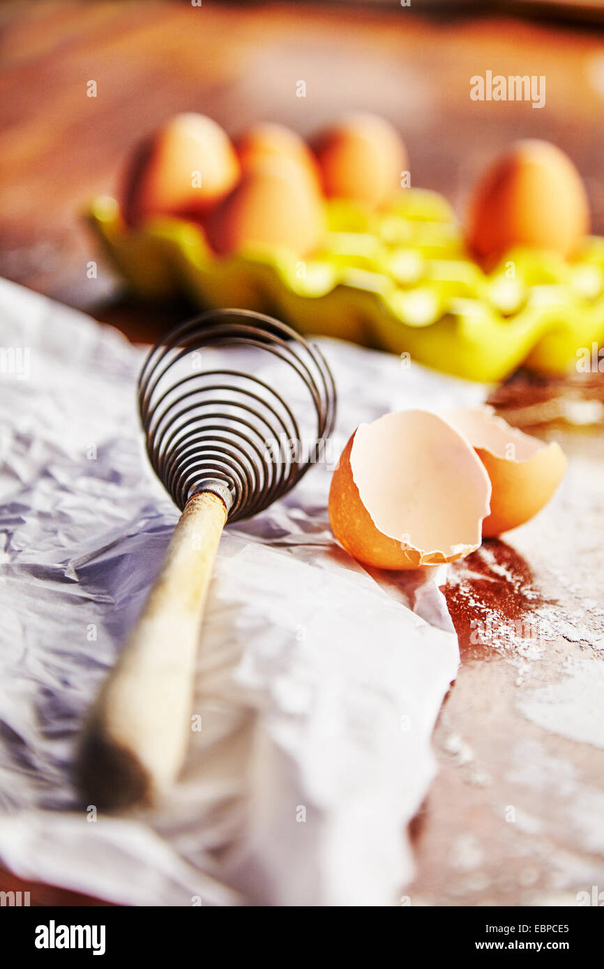 vintage whisk next to yellow egg holder over parchment paper on a wood table covered in flour - Stock Image