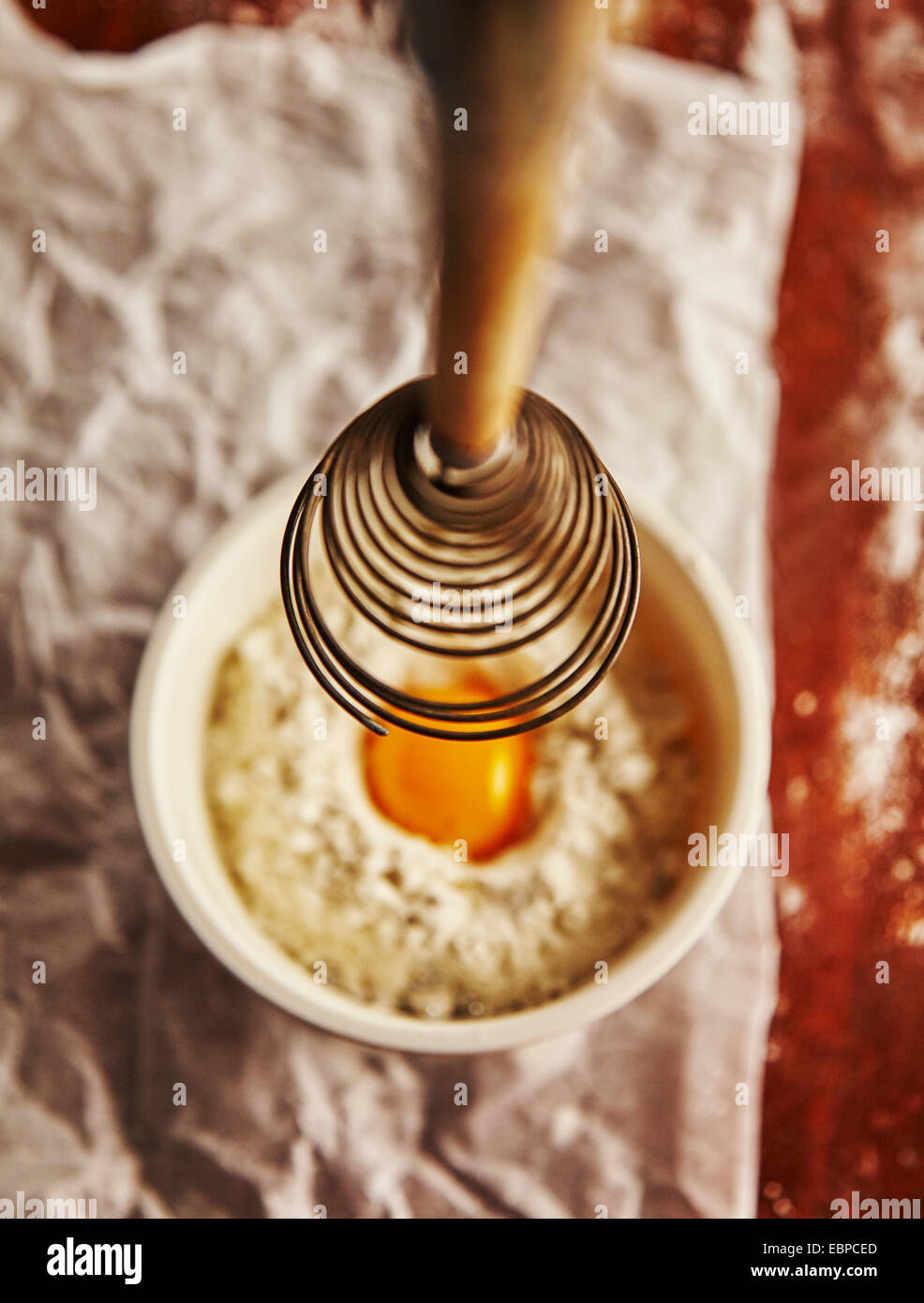 vintage whisk over a bowl with flour and an egg on top of parchment paper and wood table - Stock Image