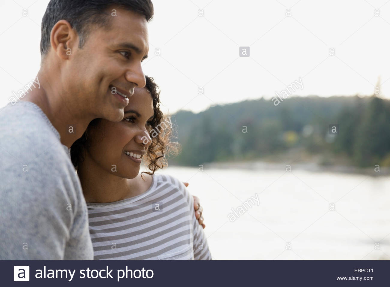 Smiling couple hugging on beach - Stock Image