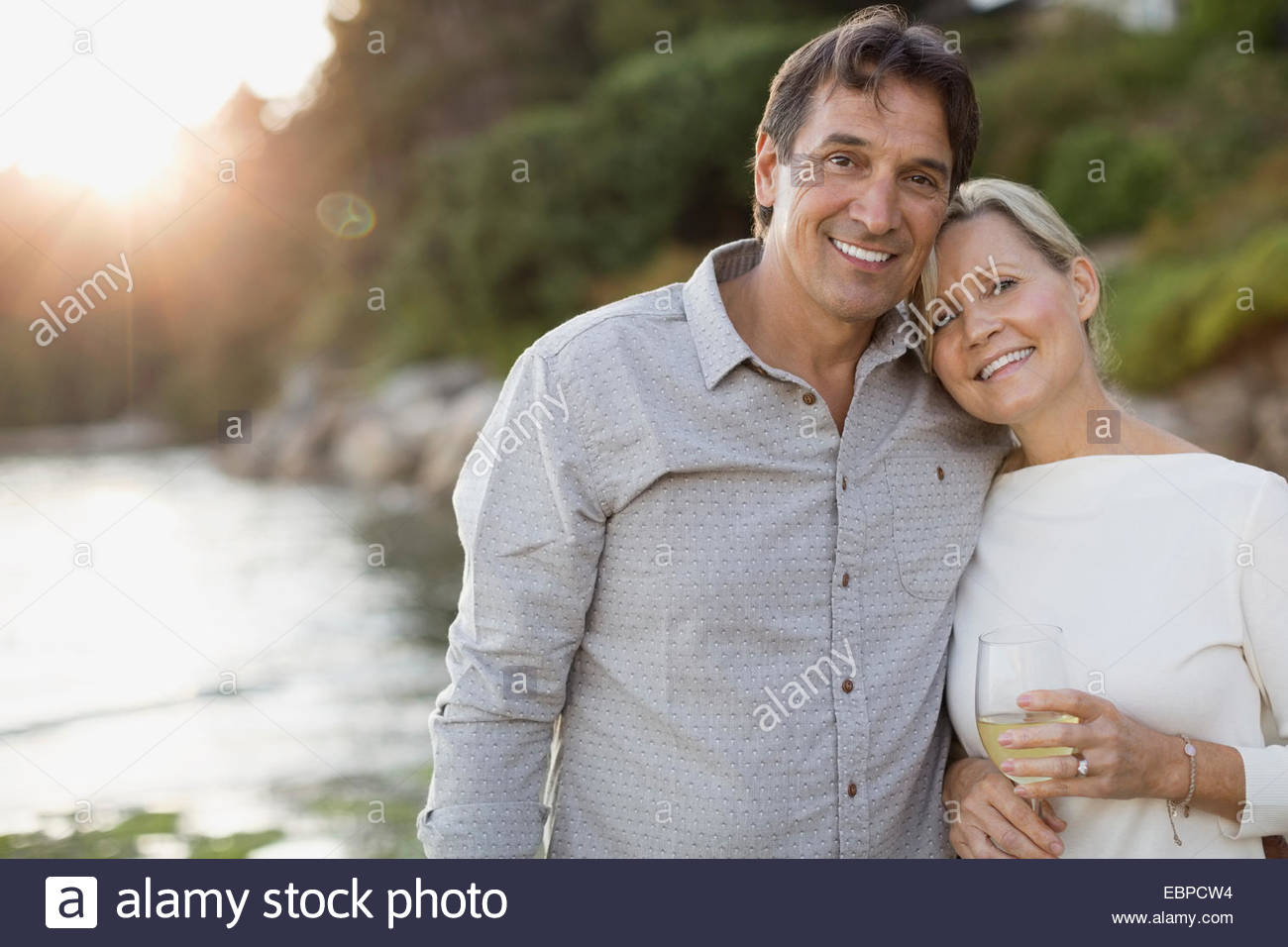 Portrait of smiling couple on beach - Stock Image
