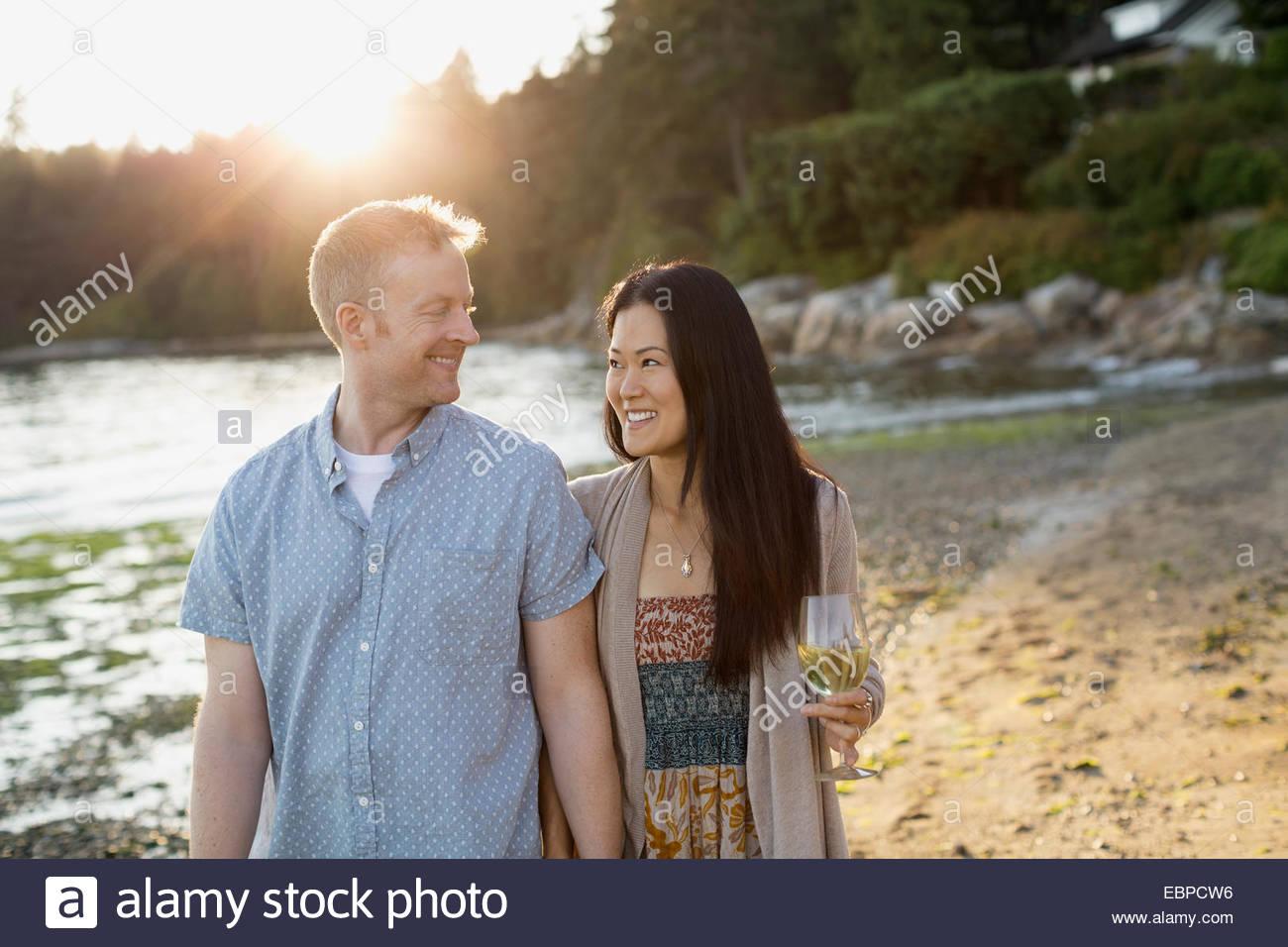 Smiling couple walking on beach - Stock Image