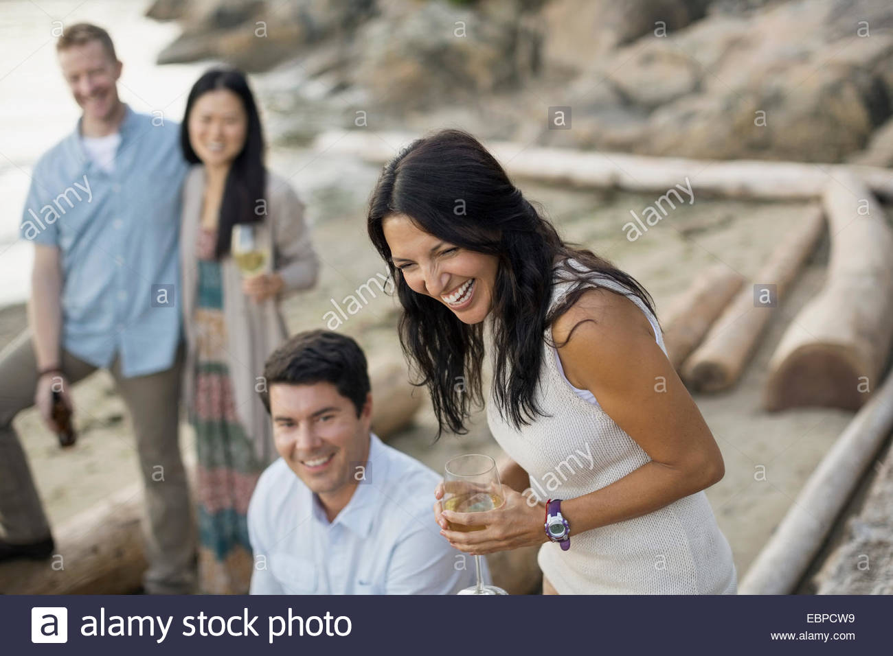 Friends drinking and laughing on beach - Stock Image