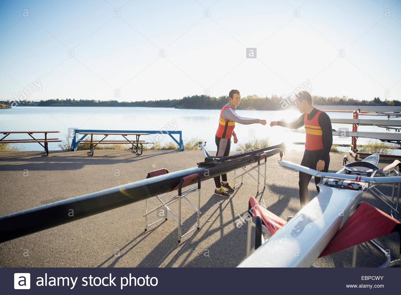 Rowers fist pumping at waterfront - Stock Image