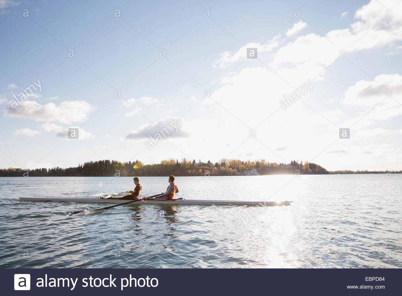 Rowing team in scull on sunny river - Stock Image