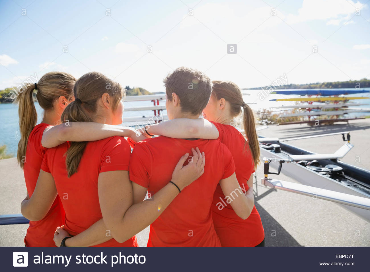 Rowing team hugging at waterfront - Stock Image