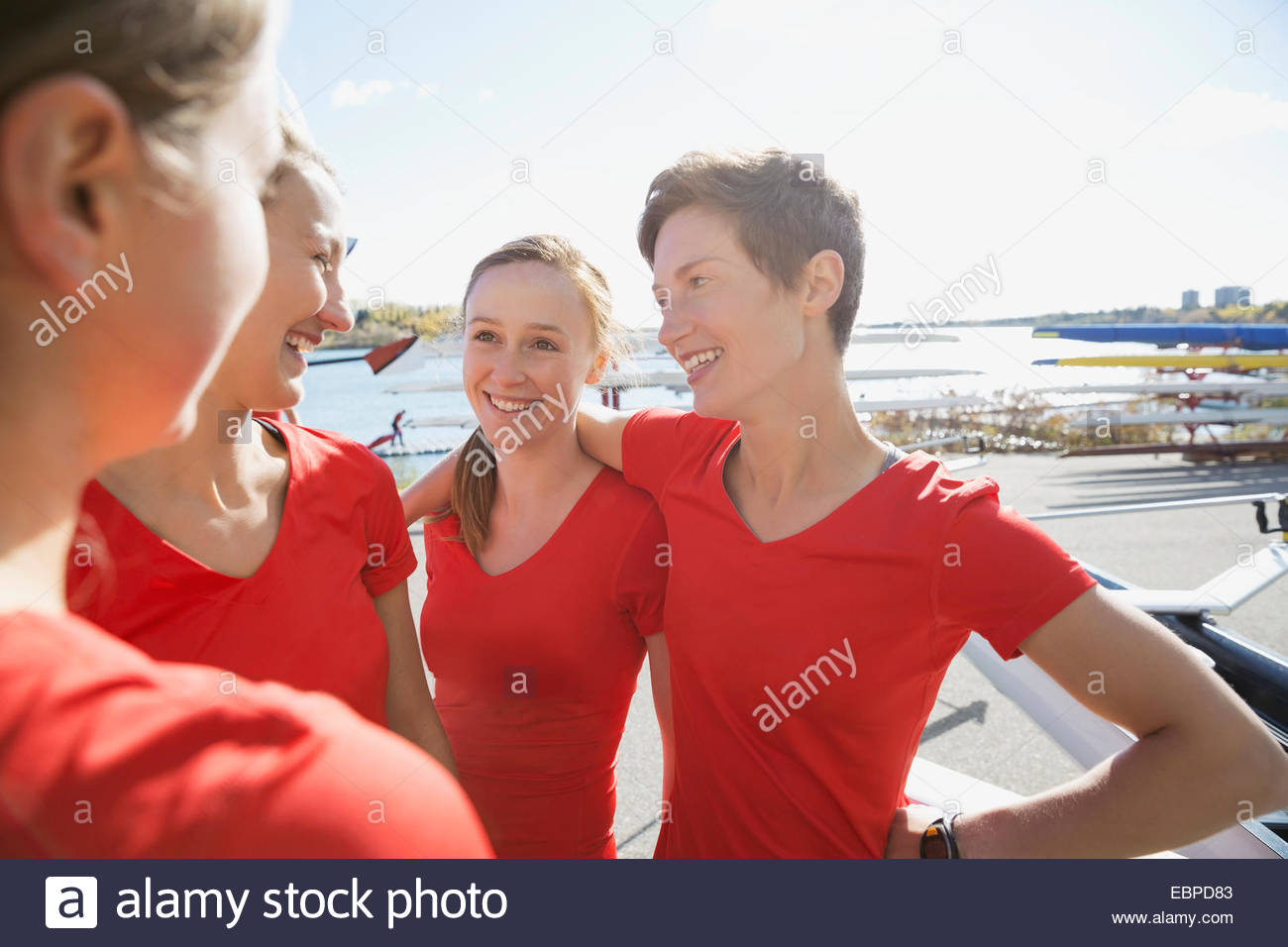 Rowing team talking at waterfront Stock Photo