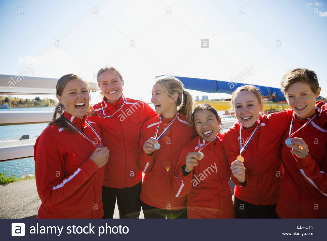 Portrait of rowing team with medals celebrating - Stock Image