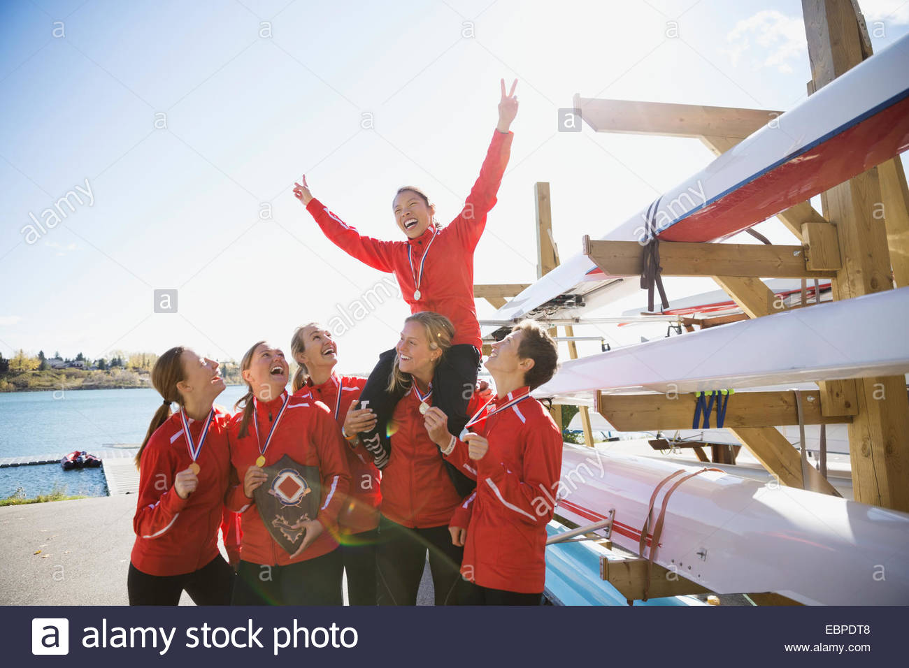 Rowing team with medals celebrating near sculls - Stock Image