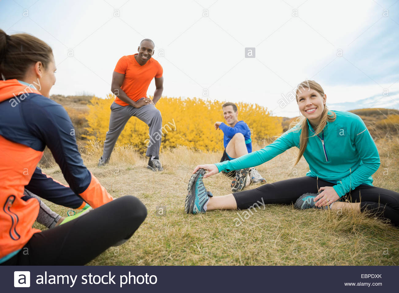 Runners stretching in field - Stock Image