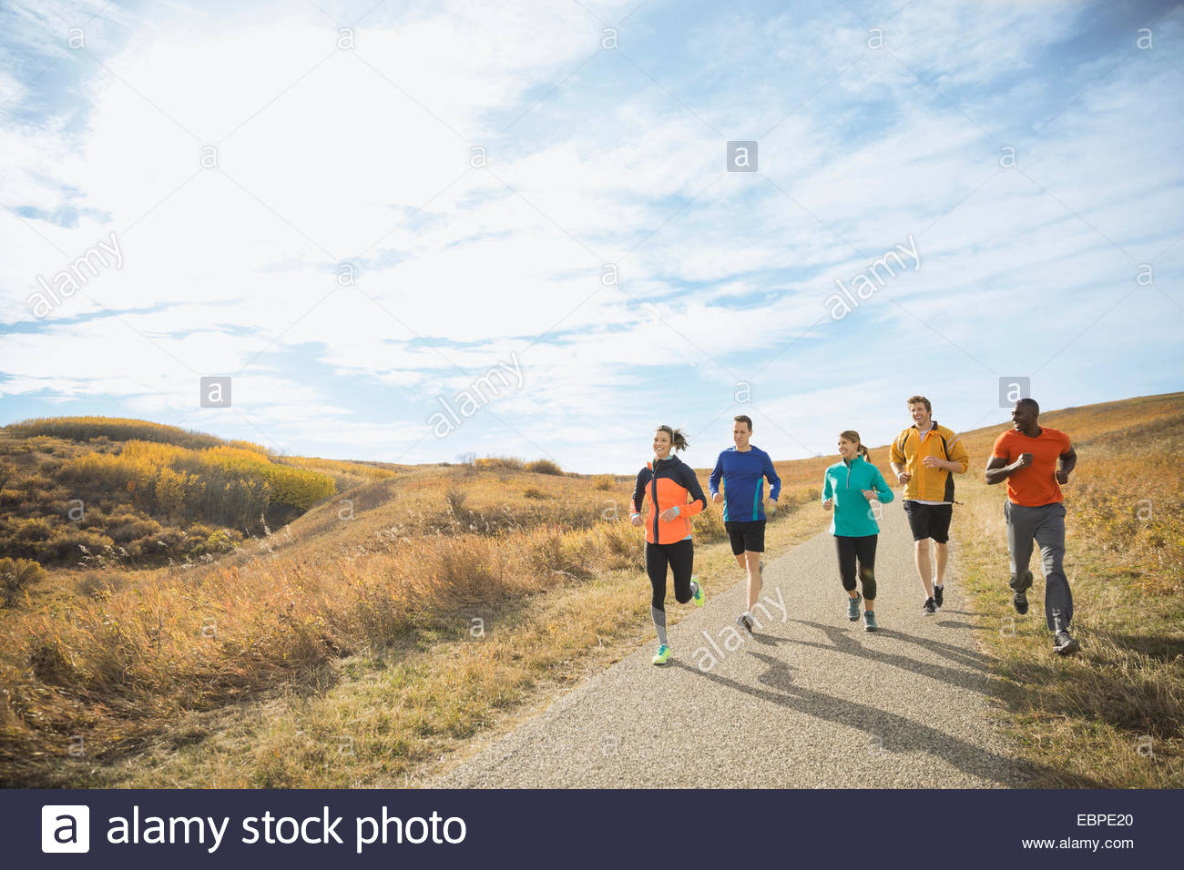 Runners on sunny rural path - Stock Image
