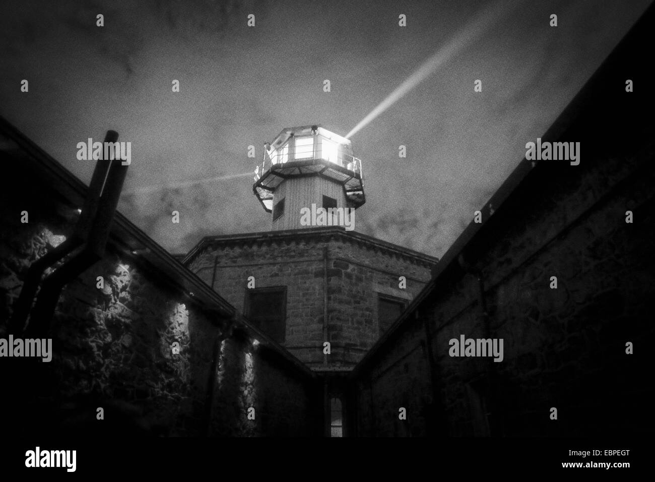 beam of light coming from the watch tower at Eastern State Prison in Philidelphia PA in the evening in black and - Stock Image