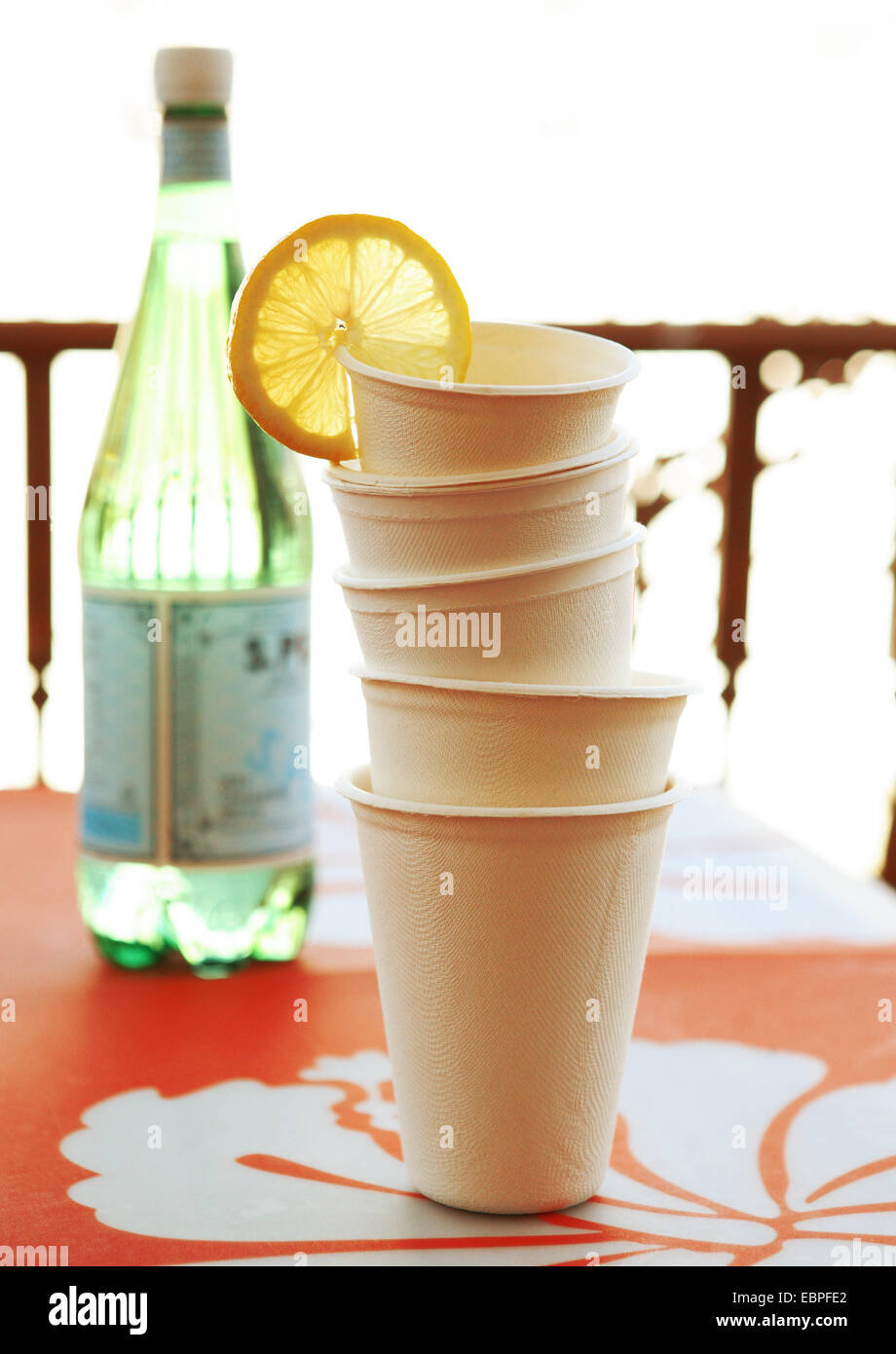 stacked disposable cups with a lemon wedge with a bottle of water on a orange place mat natural light - Stock Image
