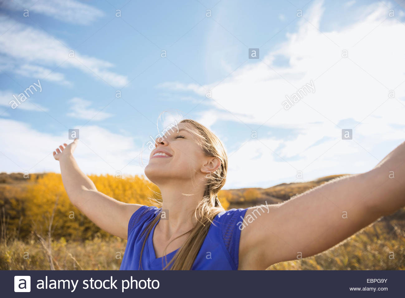 Smiling woman basking in sunlight in rural field - Stock Image