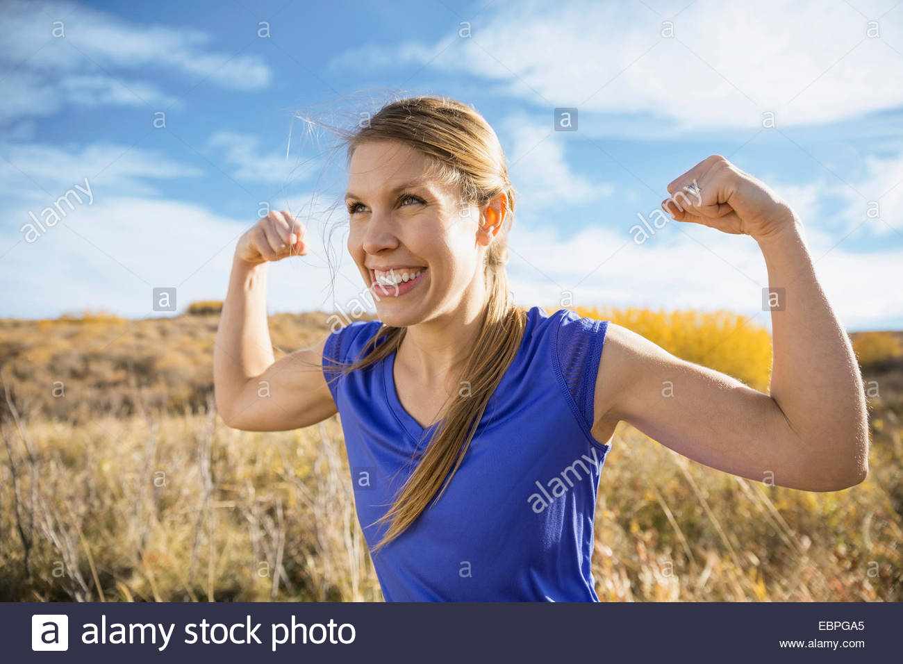 Enthusiastic woman flexing muscles in sunny rural field - Stock Image