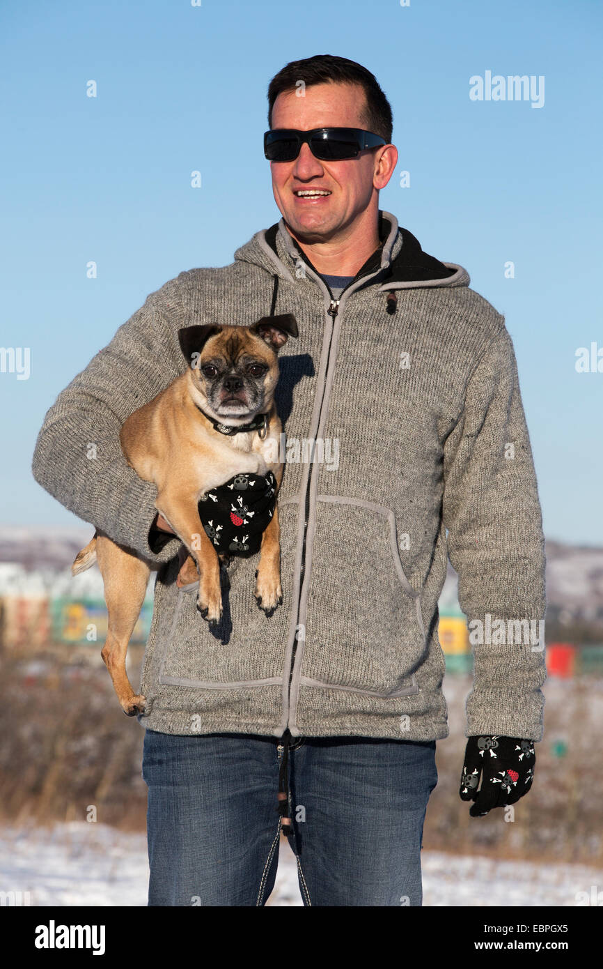 Man holding Bugg (cross between Boston Terrier and Pug) dog in city park - Stock Image