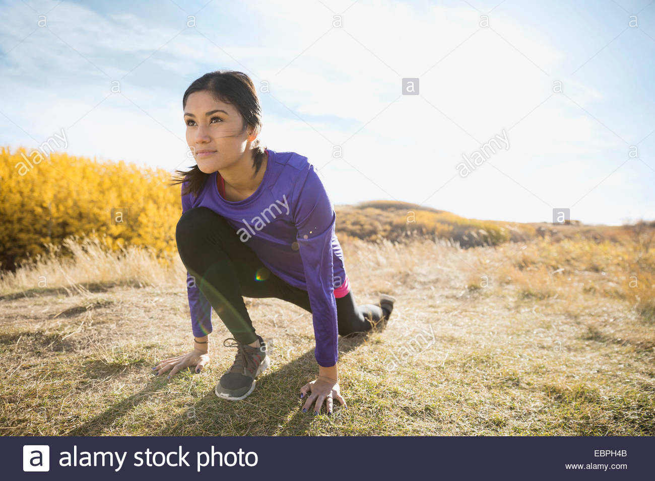 Runner stretching in sunny rural field - Stock Image