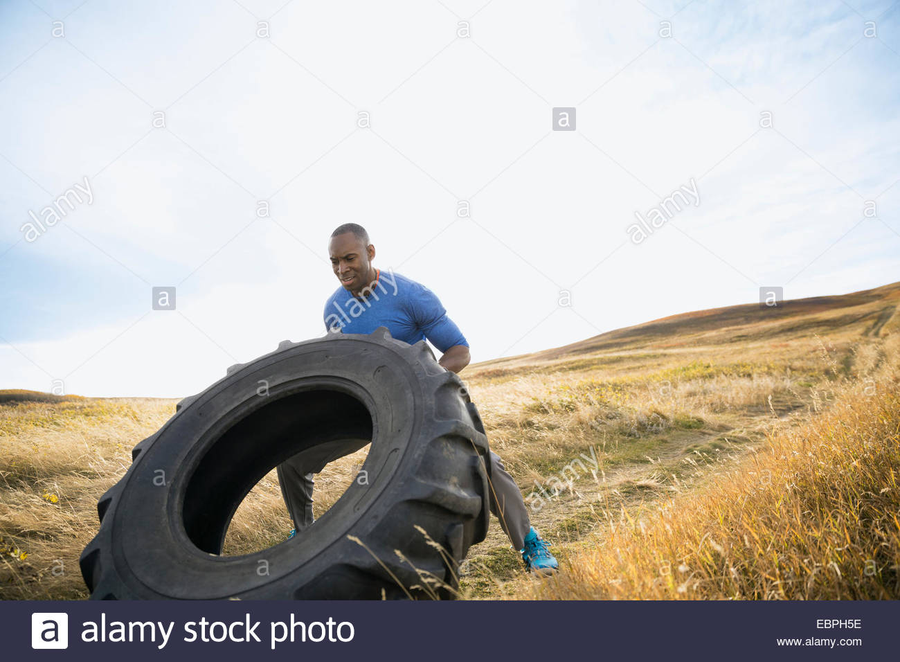 Man flipping crossfit tire in sunny rural field - Stock Image