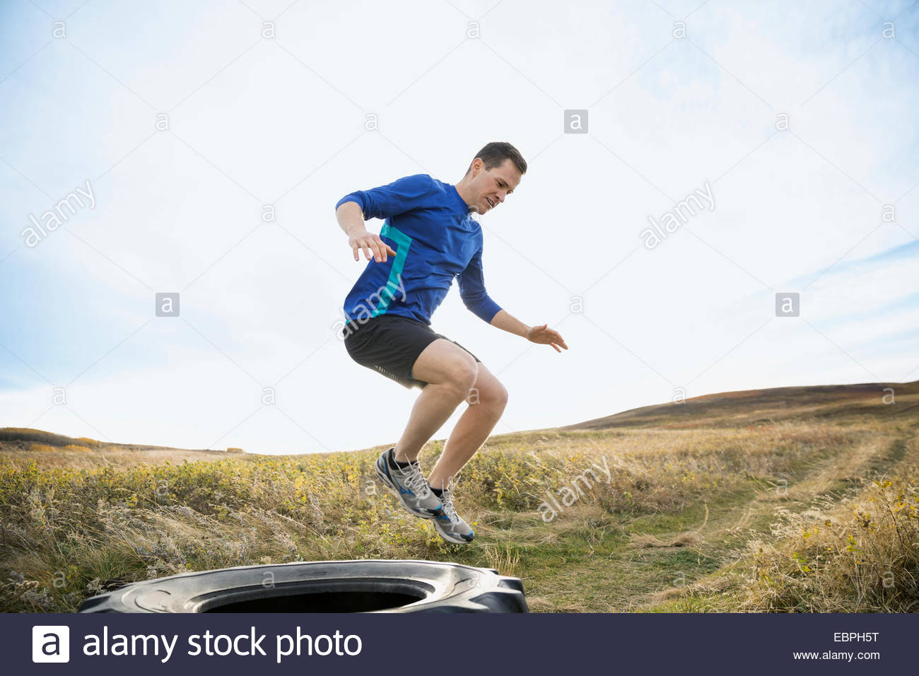 Man jumping crossfit tire in sunny rural field - Stock Image