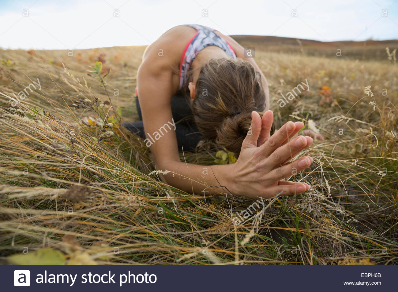 Serene woman practicing yoga in rural field - Stock Image