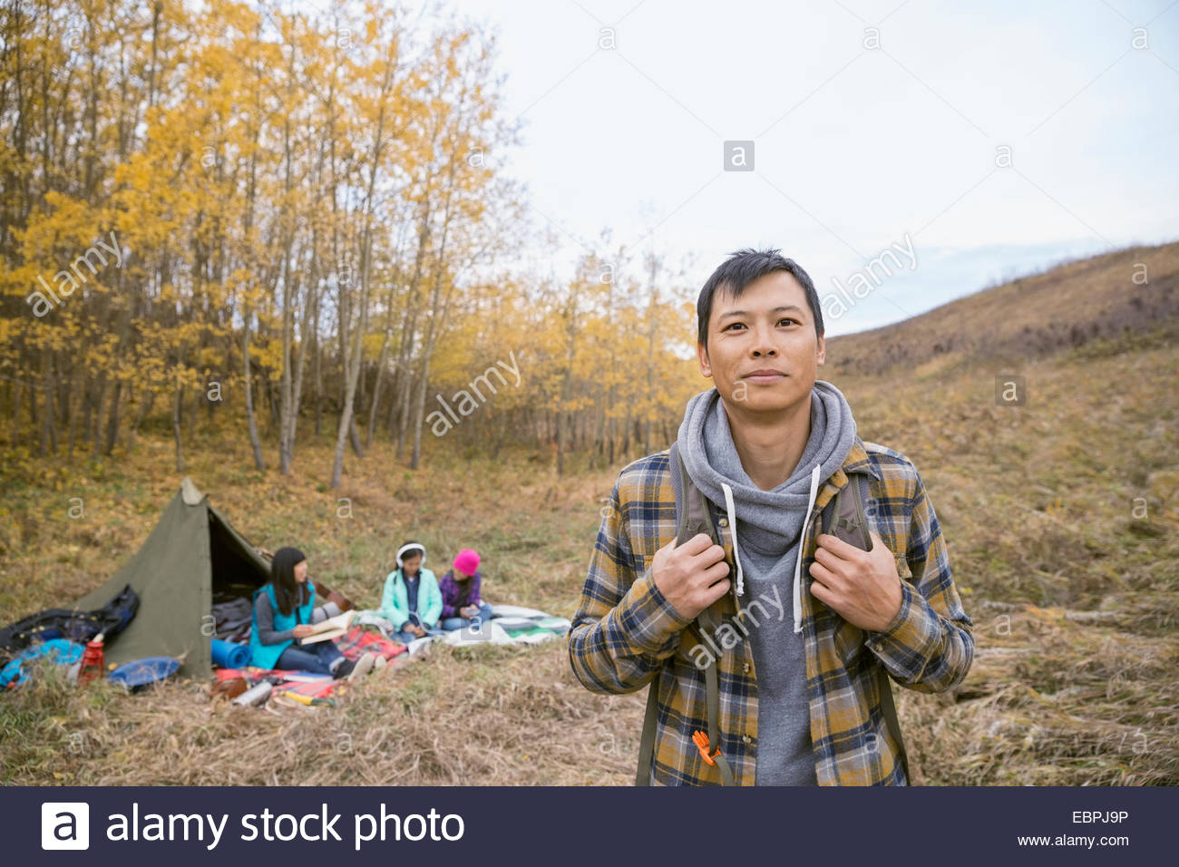 Portrait of man camping with family - Stock Image