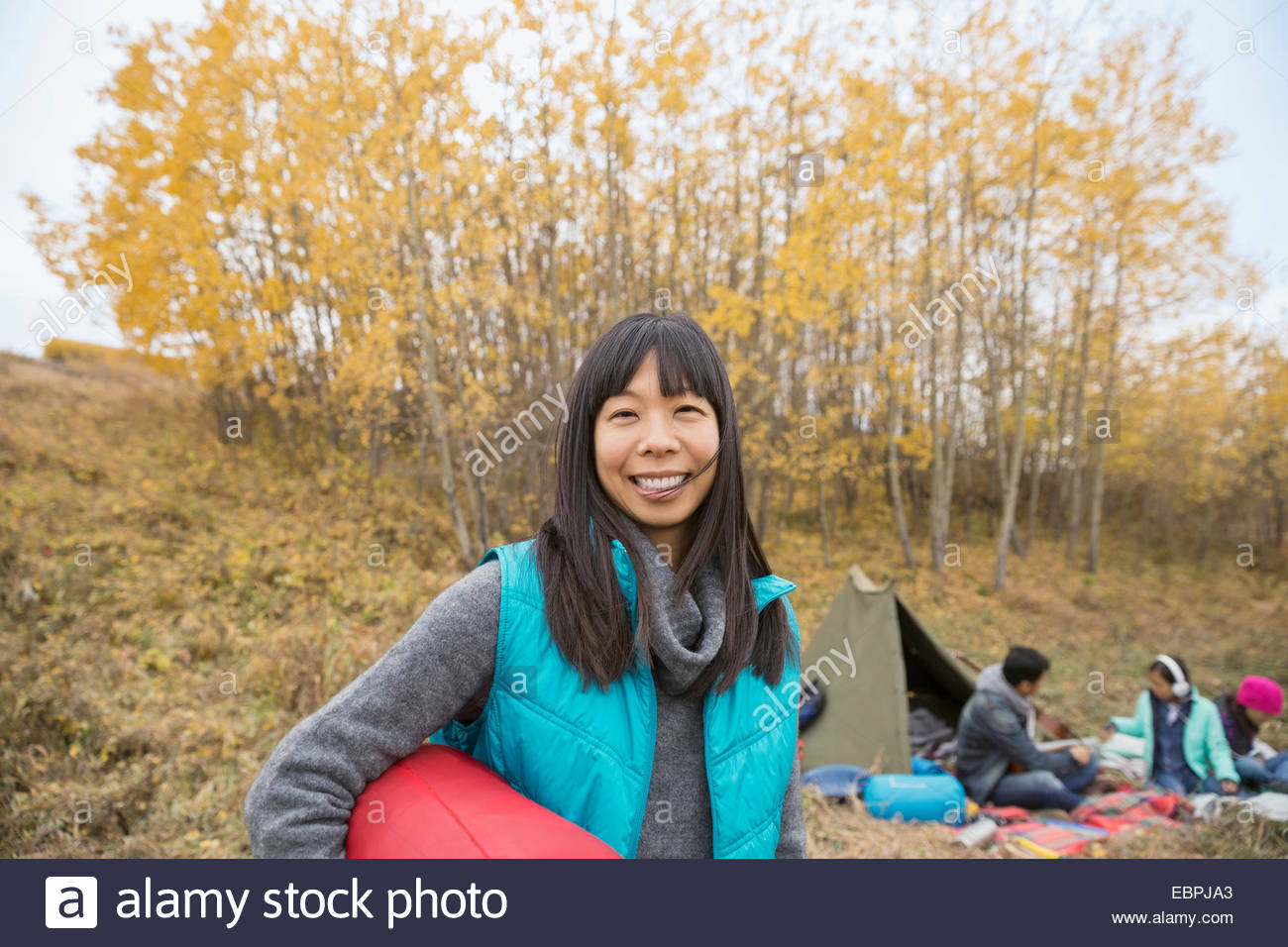 Portrait of smiling woman camping with family - Stock Image