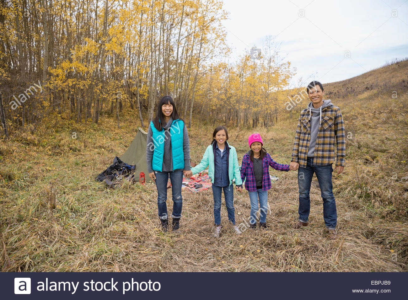 Portrait of family at campsite in rural field - Stock Image