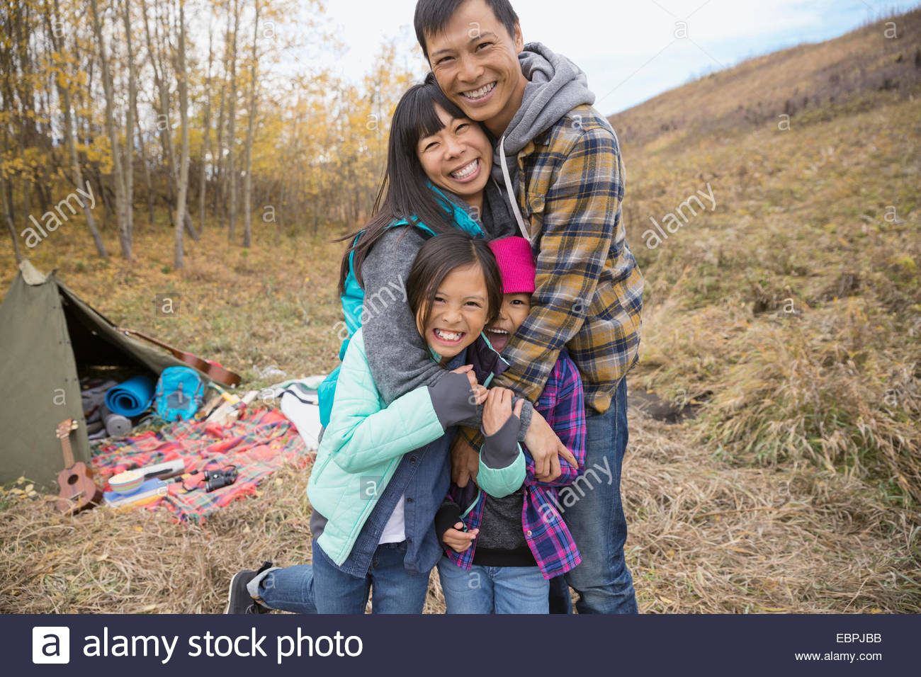 Portrait of family hugging at campsite - Stock Image
