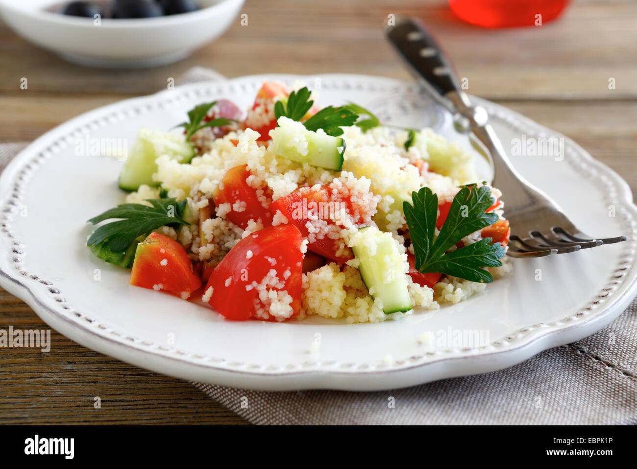 Salad with arabic couscous and vegetables on a white plate, healthy food - Stock Image