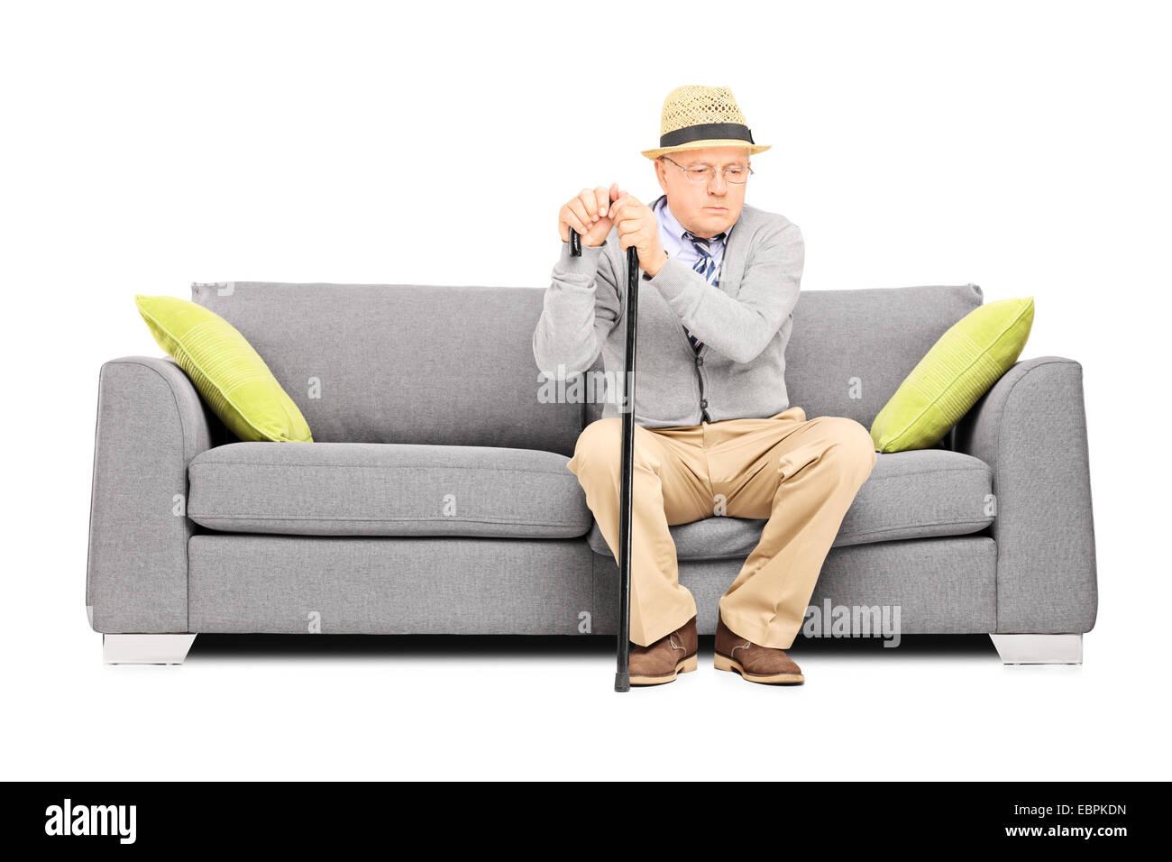 Worried senior gentleman sitting on a sofa isolated on white background - Stock Image