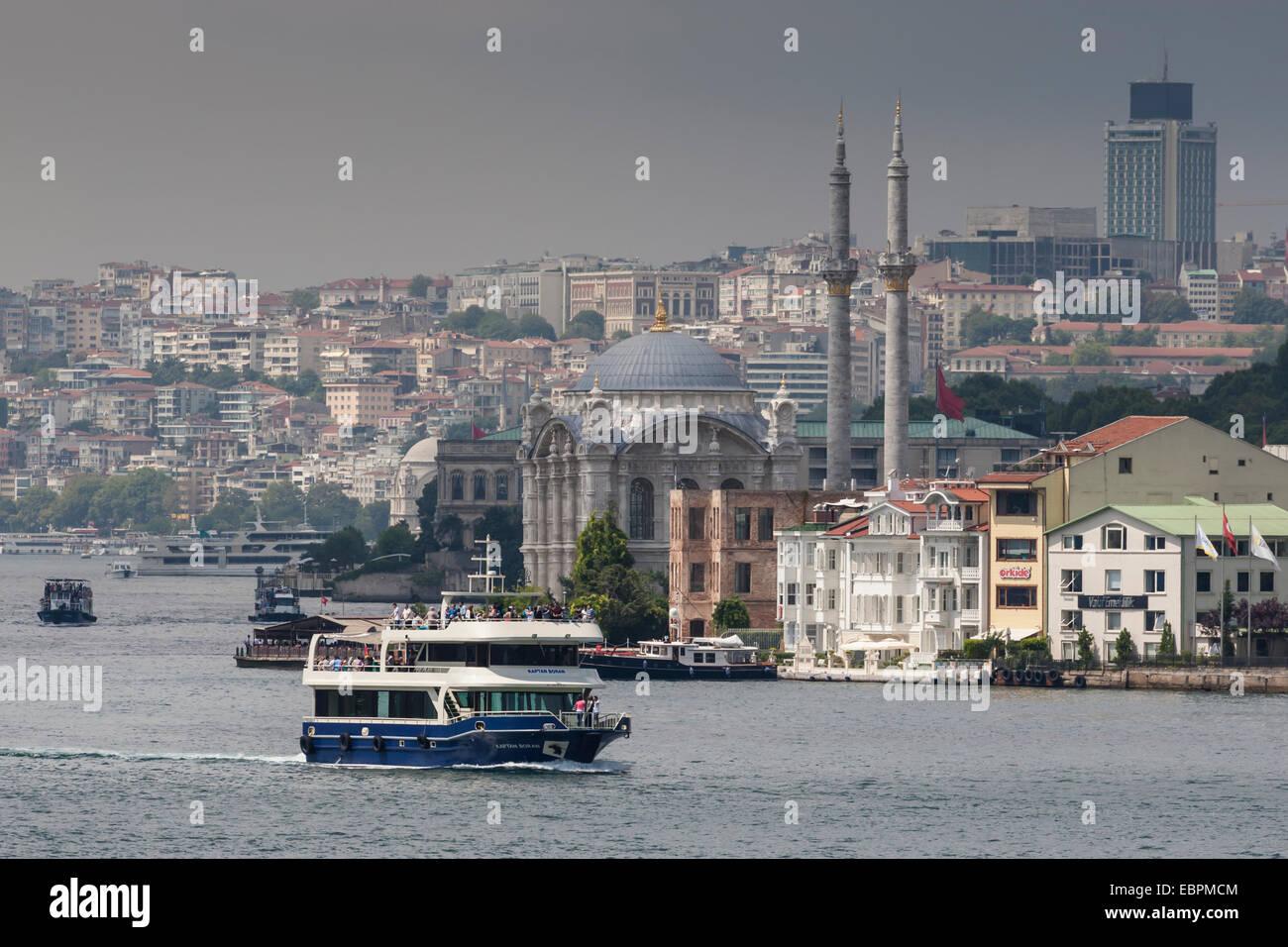 Ortakoy Mecidiye Mosque and passenger ferry, Ortakoy, from Bosphorus Strait with Istanbul city skyline behind, Istanbul, - Stock Image