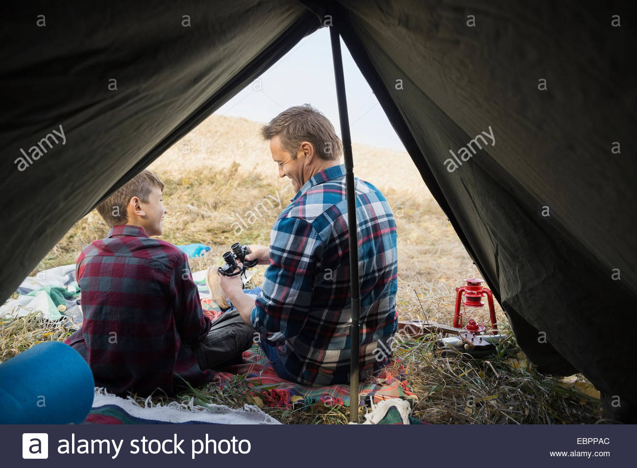Father and son with binoculars outside tent - Stock Image