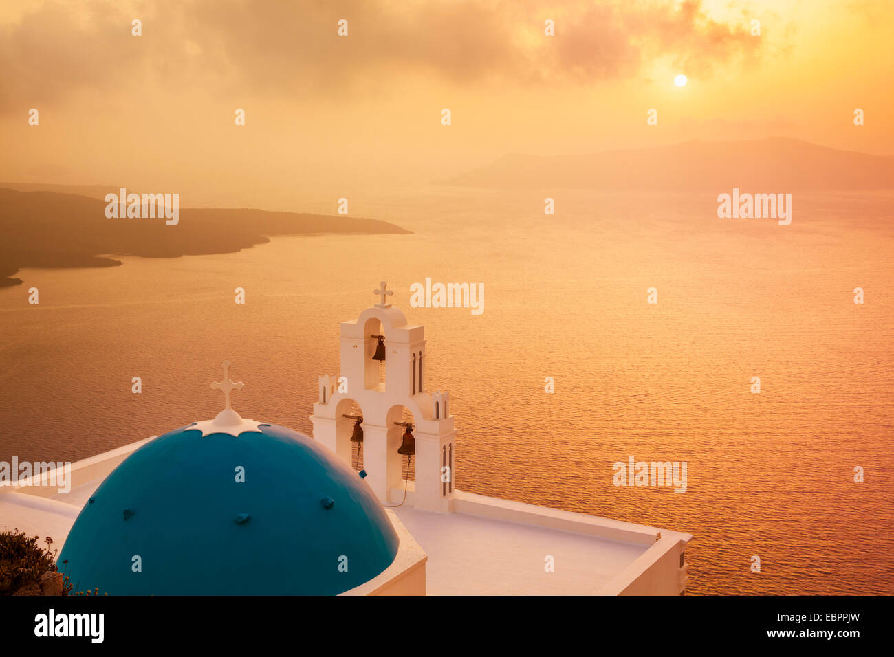 Blue dome and bell tower at sunset, St. Gerasimos church and Aegean Sea, Firostefani, Fira, Santorini, Cyclades Stock Photo