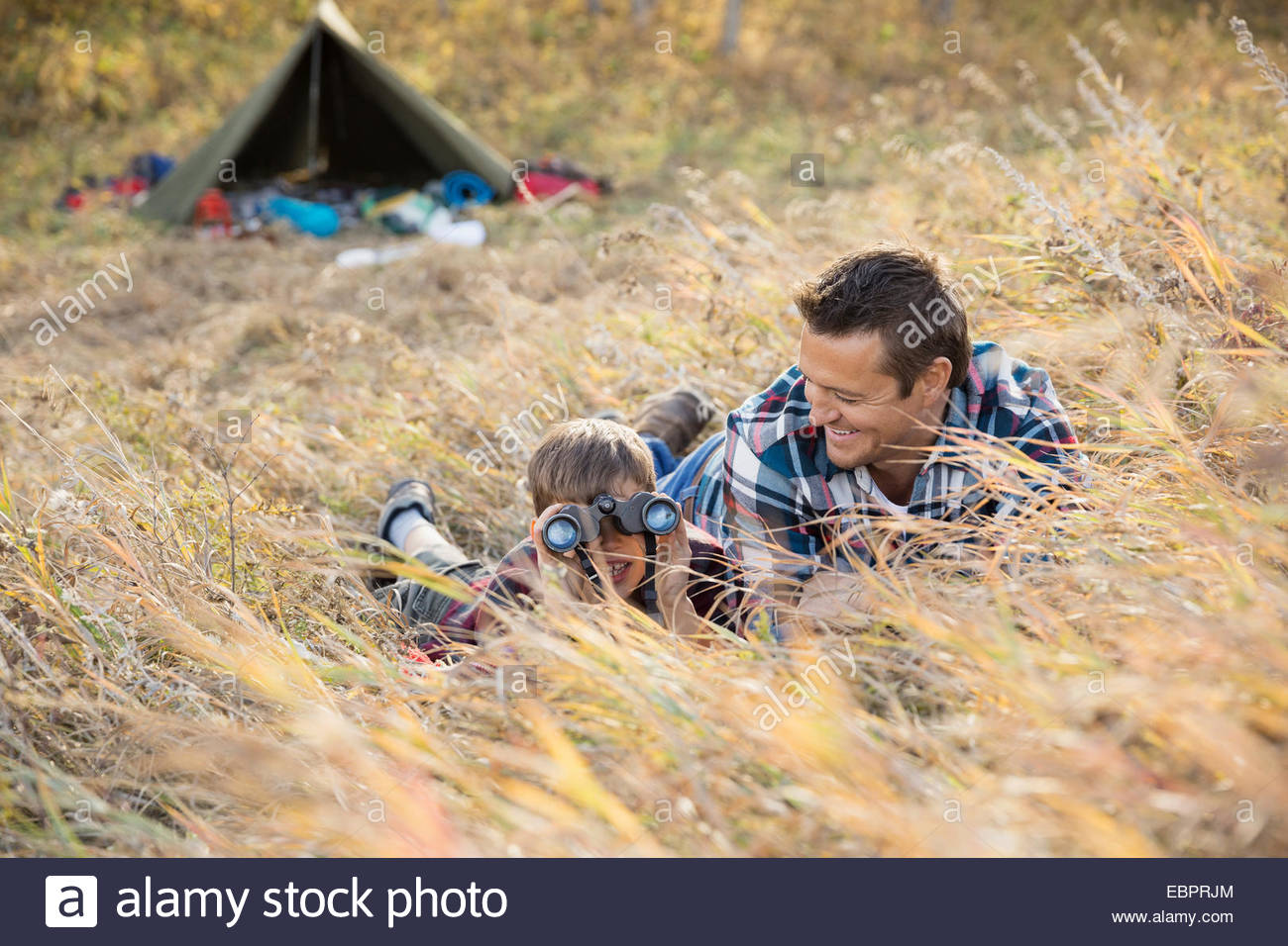 Father and son using binoculars outside tent - Stock Image