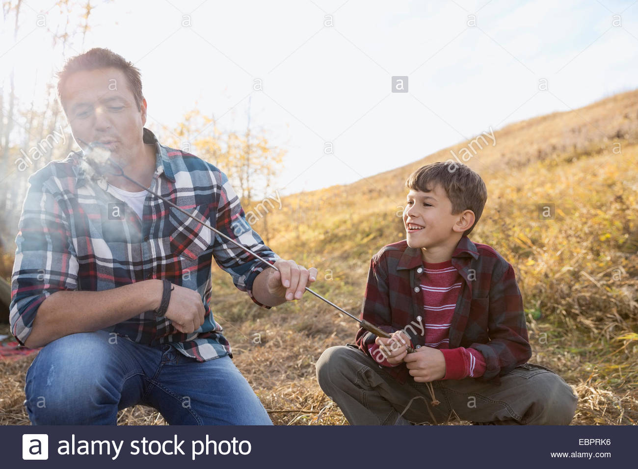 Father and son roasting marshmallows - Stock Image