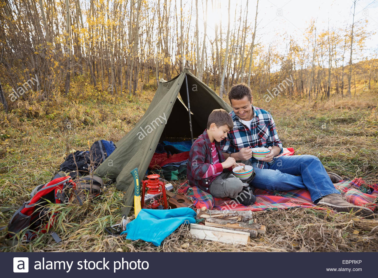 Father and son eating outside tent at campsite - Stock Image