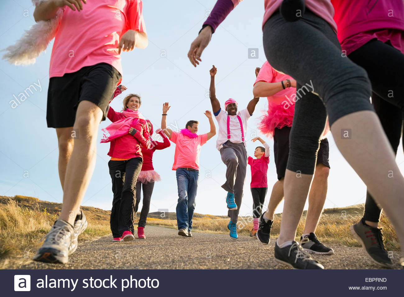 Group in pink walking at charity race - Stock Image