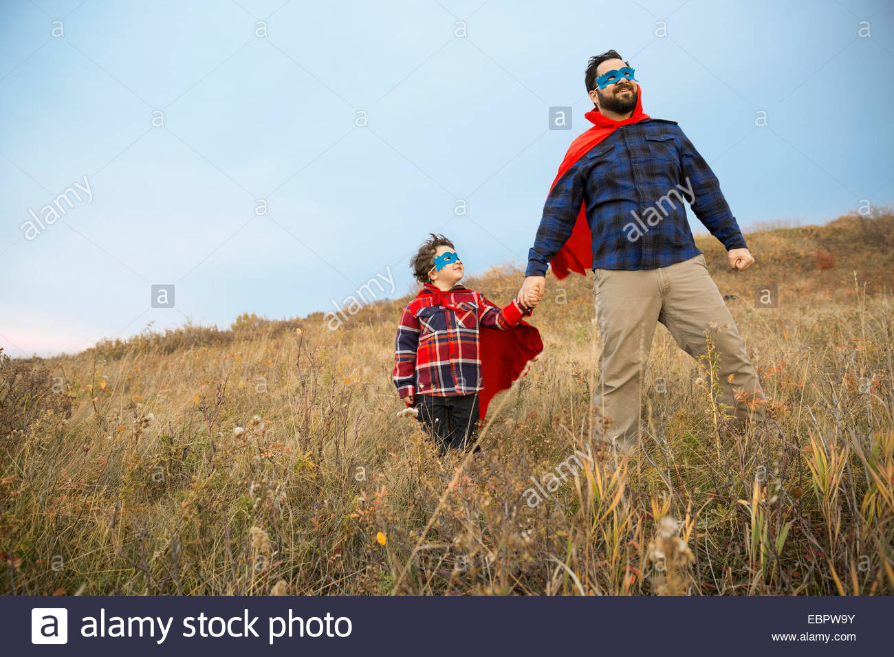 Father and son in superhero capes in field - Stock Image