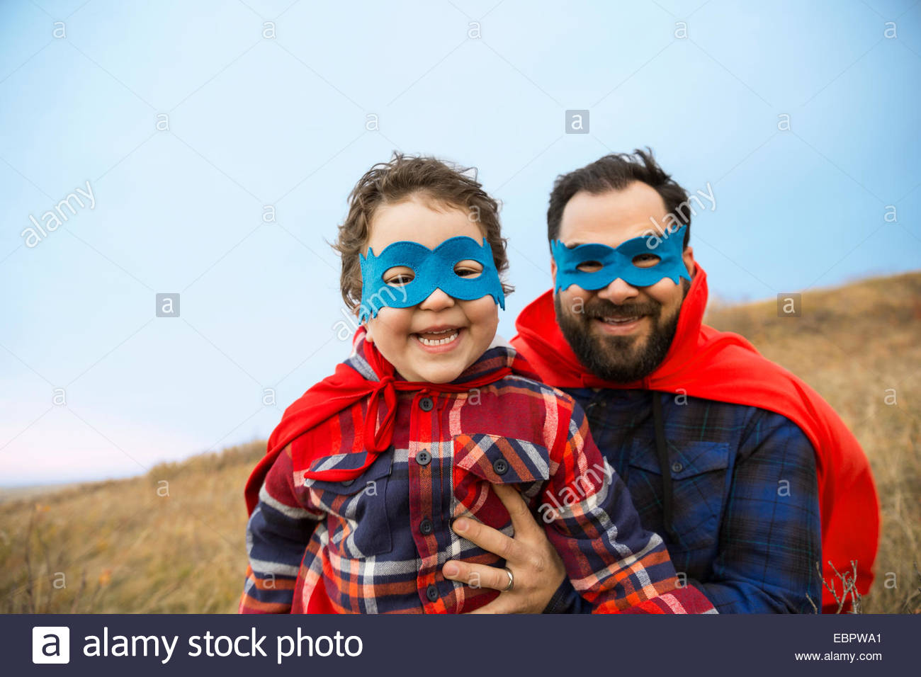 Portrait of father and son in superhero capes - Stock Image