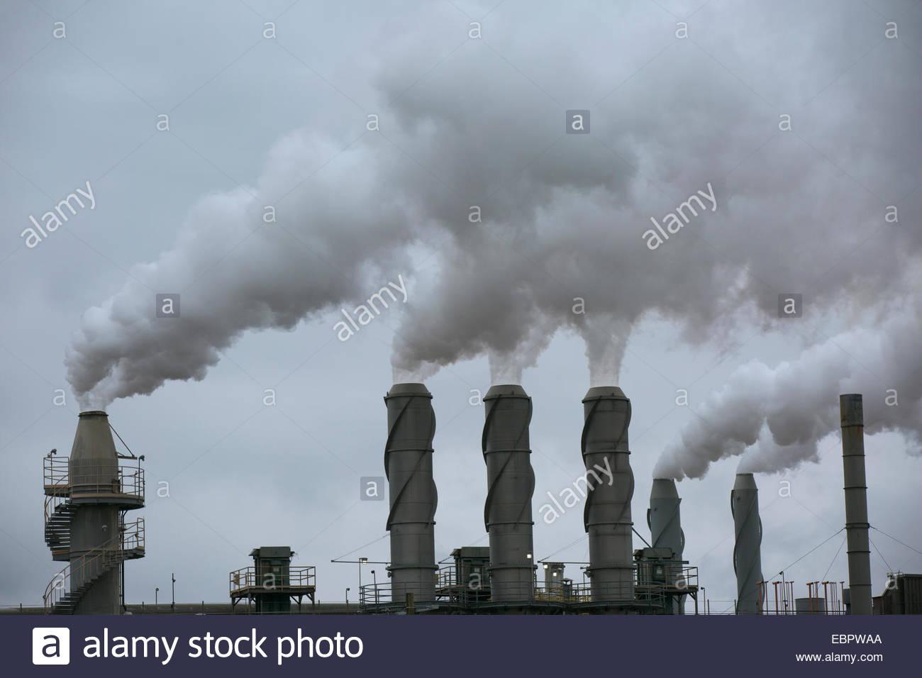 Smoke emitting from smokestacks Stock Photo