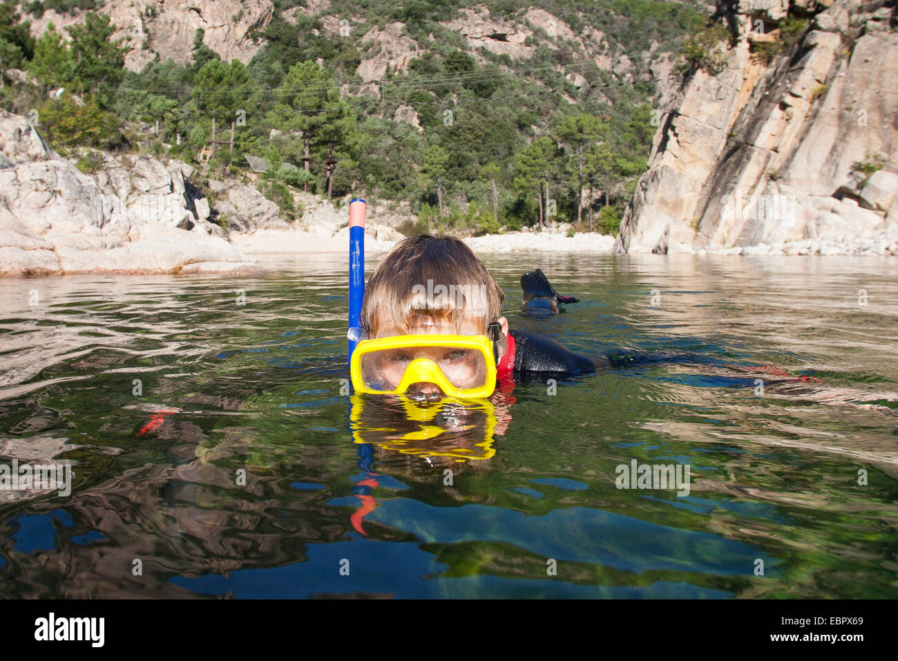 boy snorkeling in a crystal clear stream, France, Corsica - Stock Image