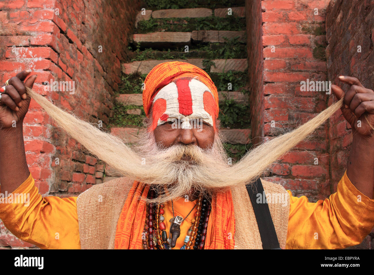 sadhu monk holding up his hairs of the beard, Nepal, Kathmandu, Pashupatinath - Stock Image