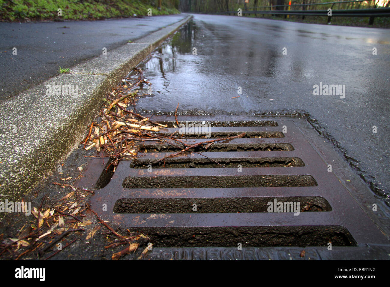 rain water streaming into a gully hole, Germany - Stock Image