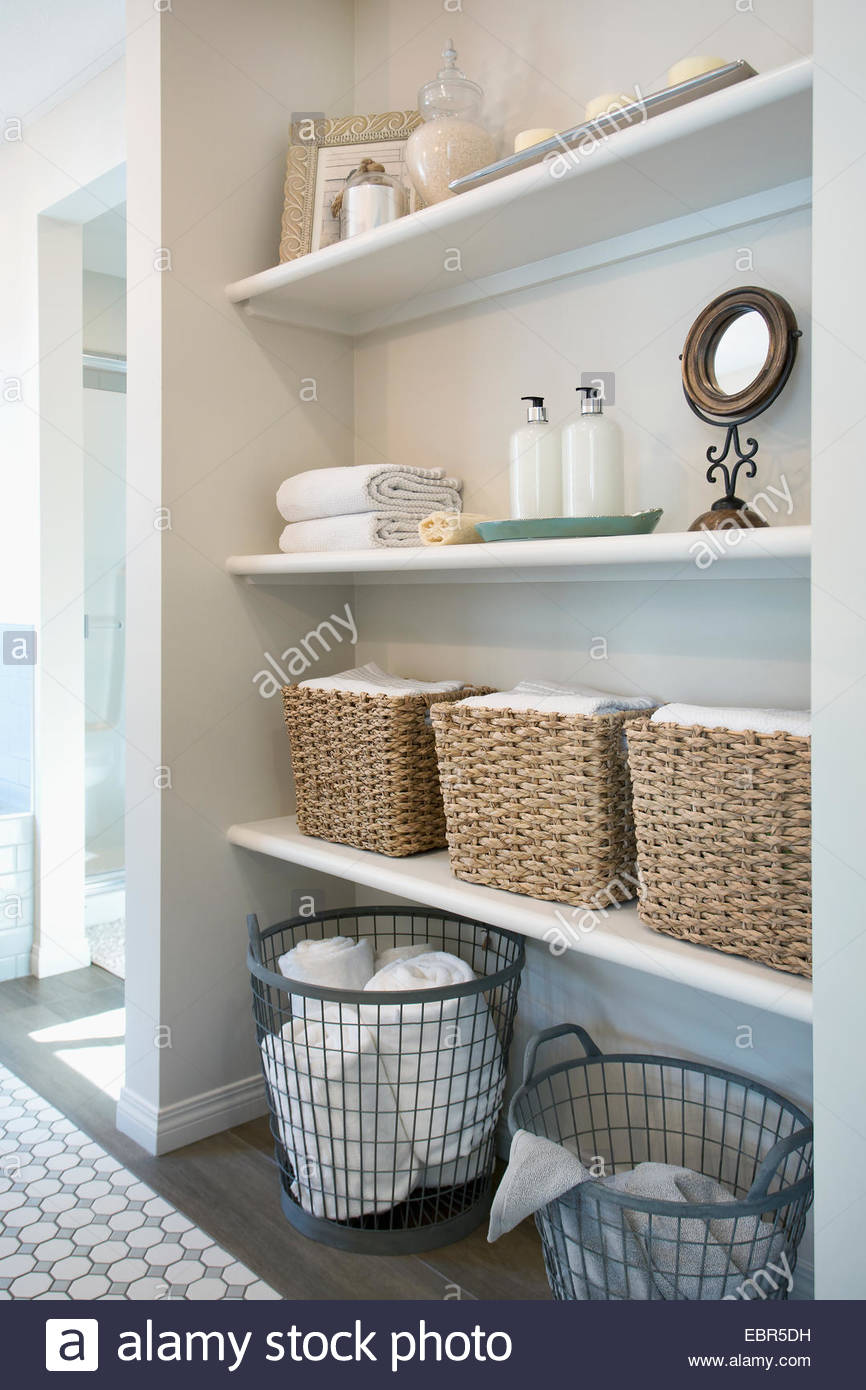 Baskets and items on bathroom shelves - Stock Image