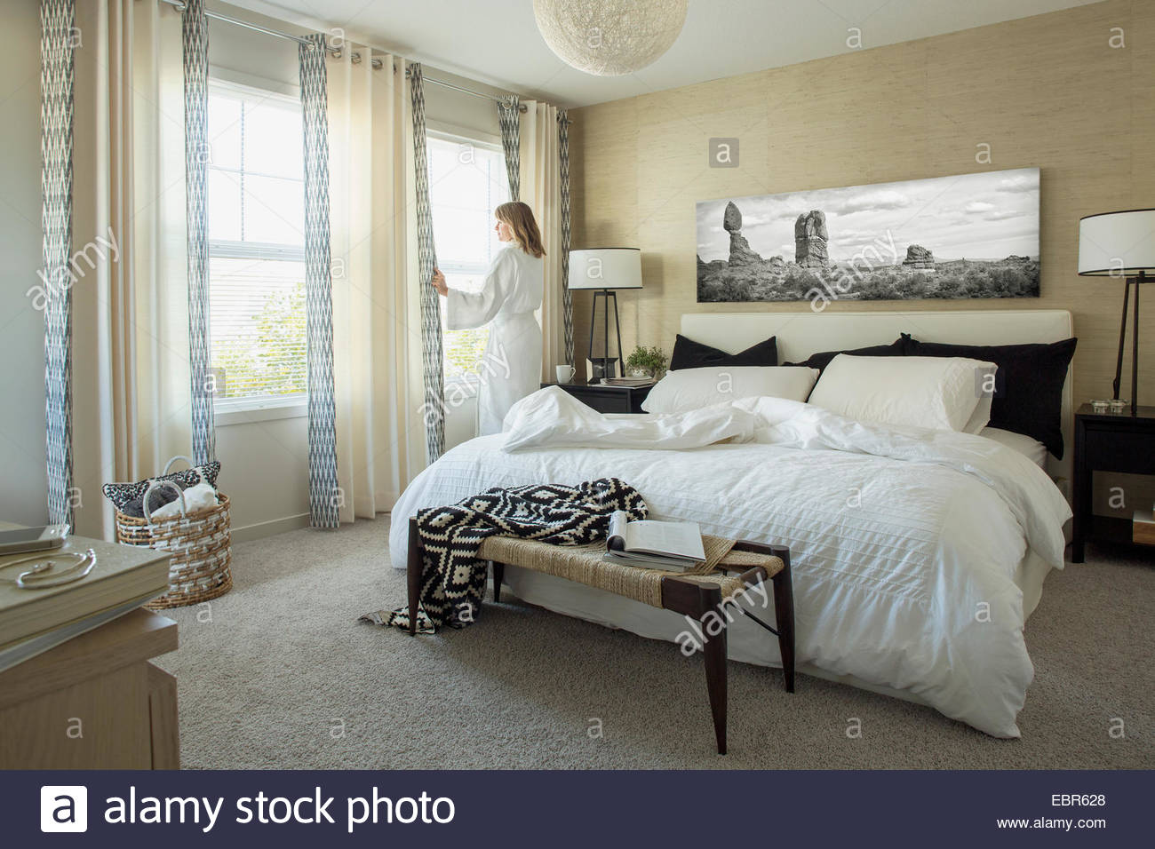 Woman in bathrobe at bedroom window - Stock Image