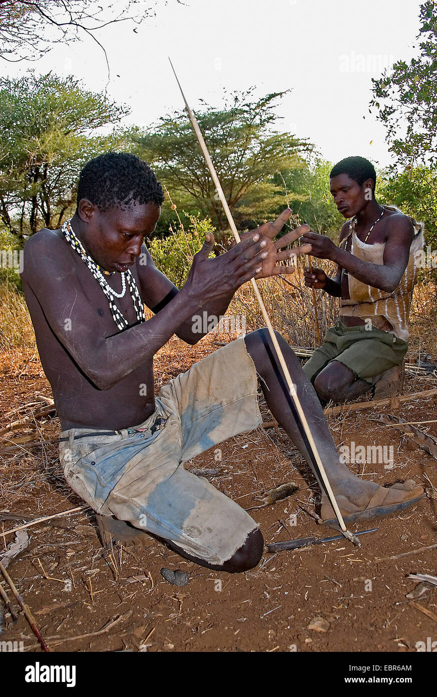 Hadzabe bushmen making up fire with a stick, Tanzania - Stock Image