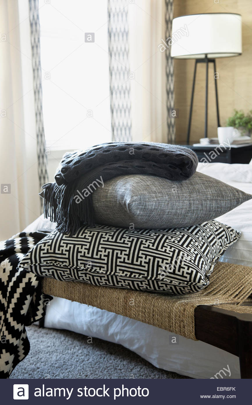 Pillows and blanket stacked on bench in bedroom - Stock Image