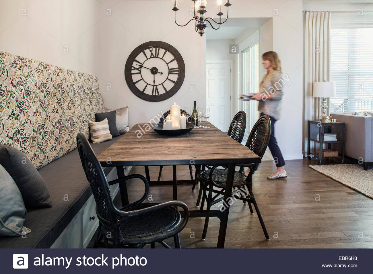 Woman walking toward table in dining room - Stock Image