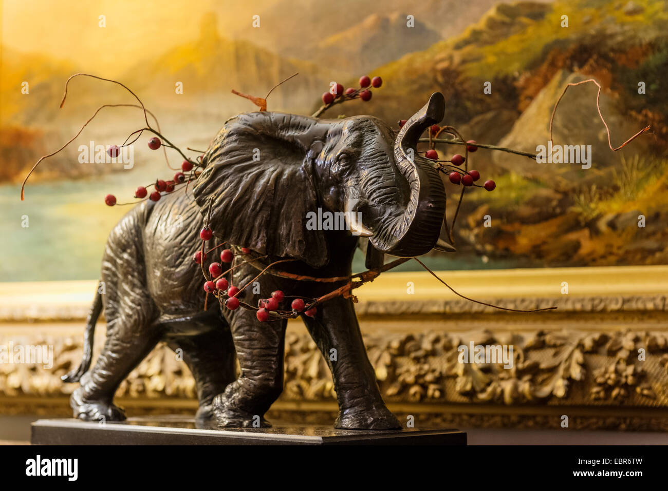 a sprig of holly adds a festive touch to a statue of an elephant - Stock Image