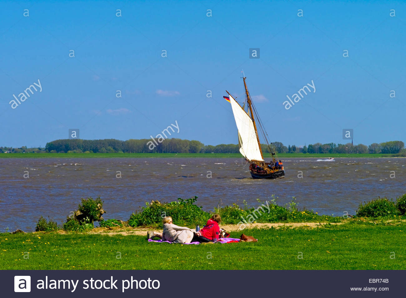 two persons resting at the riverside of the Elbe watching the traditionel ship mytilus, Germany, Lower Saxony - Stock Image